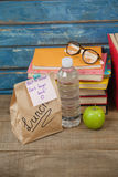 Stack of books, apple, water bottle, spectacles and lunch bag Stock Photo