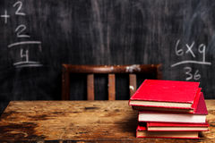 Stack of books by blackboard with bad math. Stack of red books on school desk with blackboard in the background royalty free stock images