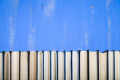 Stack of books on a blue background. Royalty Free Stock Photo