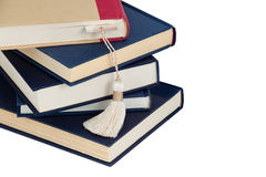 A stack of books and a bookmark. Isolated in white Stock Photos