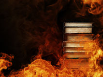 Stack of books in a burning fire. Conceptual image of a tall stack of hardcover books in a burning fire with flames and smoke swirling around them in a darkened Stock Photo