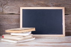Stack of books and chalk board on a wooden table Royalty Free Stock Photos