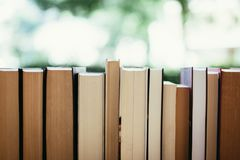 Stack of books at a charity book flea market, text space. Stack of books, blurry background: Charity book flea market, outdoors. Text space sale education buying royalty free stock image