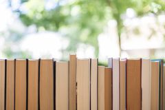 Stack of books at a charity book flea market, text space. Stack of books, blurry background: Charity book flea market, outdoors. Text space sale education buying royalty free stock images