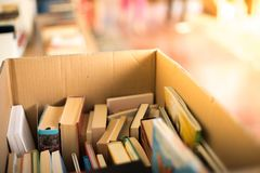 Stack of books at a charity book flea market, text space. Stack of books, blurry background: Charity book flea market, outdoors. Text space sale education buying stock photos