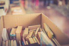 Stack of books at a charity book flea market, text space. Stack of books, blurry background: Charity book flea market, outdoors. Text space sale education buying royalty free stock photography