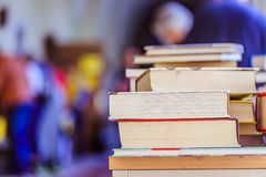 Stack of books at a charity book flea market, text space. Stack of books, blurry background: Charity book flea market, outdoors. Text space sale education buying stock image