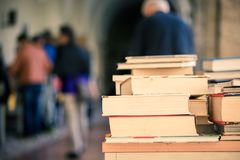 Stack of books at a charity book flea market, text space. Stack of books, blurry background: Charity book flea market, outdoors. Text space sale education buying stock photography