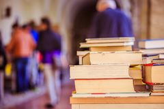 Stack of books at a charity book flea market, text space. Stack of books, blurry background: Charity book flea market, outdoors. Text space sale education buying royalty free stock photos