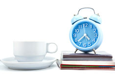 Stack of books, clock and cup Stock Image