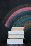 Stack of books with colorful chalkboard in background. School concept. Stack of books close up on wooden desk with multicolor  chalkboard as background. Space Royalty Free Stock Image