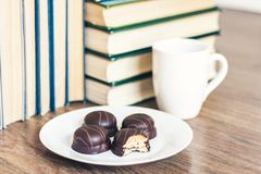 Stack of books, cup of coffee and chocolate cookies white plate stock image