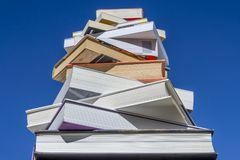 Stack of books of descending magnitude against a beautiful blue sky. On a sunny day stock images