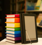 Stack of books with e-book reader. Stack of books with electronic book reader Stock Photography