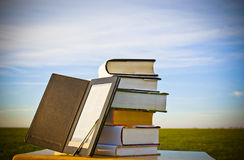 Stack of books with ebook reader. Outdoors laying on table Stock Images