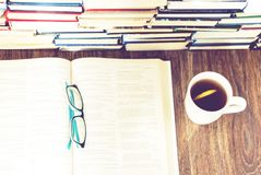 Stack of books education background, open book, glasses, and cup of tea with lemon stock photography