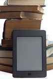 STACK OF BOOKS AND ELECTRONIC BOOK READER. Royalty Free Stock Images