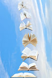 Stack of books fly in blue sky Stock Image