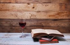 A Stack of books and A glass of Red wine. With a wooden background Stock Images