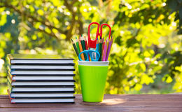 A stack of books and glass stationery. A stack of books and stationery with a glass on a wooden table. Green background blur. Royalty Free Stock Images