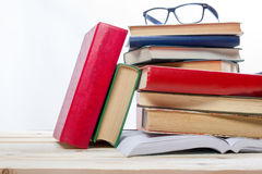 Stack of books and glass on wooden table isolated on white background. Back to school. Copy space.  Stock Photos