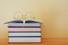 Stack of books and glasses. Stack of colorful books one open book and round metallic frame glasses on wooden bookshelf in home on yellow wall background with stock images