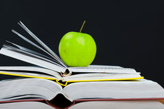 Stack of books with green apple Stock Photos