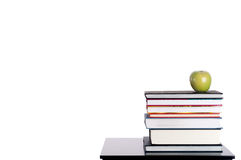 A stack of books with a green apple on white Royalty Free Stock Photography