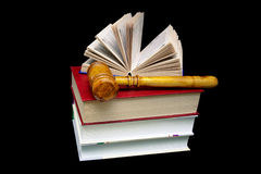 Stack of books and a hammer judge on a black background Royalty Free Stock Photos