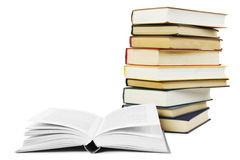 Stack of books in hard cover and one opened book. In front, isolated royalty free stock image