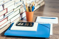 Stack of books, hardback books, smartphone, plastic folder, notebook and pencils on wooden table copy space for text.  royalty free stock photo