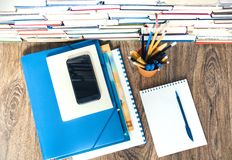 Stack of books, hardback books, smartphone, plastic folder, notebook and pencils on wooden table copy space for text.  stock photo