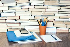 Stack of books, hardback books, smartphone, plastic folder, notebook and pencils on wooden table copy space for text.  stock photography