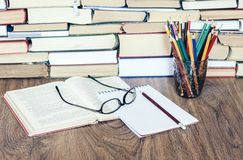 Stack of books, hardback books on wooden table, open book, notebook and glasses, copy space for text.  stock image