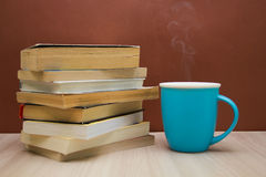 A stack of books and a hot drink in a blue mug Stock Photos