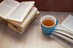 A stack of books and a hot drink in a blue mug Stock Images