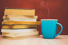 A stack of books and a hot drink in a blue mug Royalty Free Stock Images