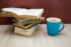 A stack of books and a hot drink in a blue mug Royalty Free Stock Image