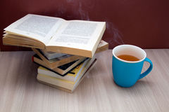 A stack of books and a hot drink in a blue mug Royalty Free Stock Photo