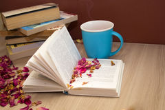 A stack of books and a hot drink in a blue mug Stock Image