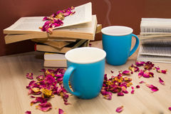 A stack of books and a hot drink in a blue mug Stock Photography