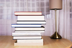 Stack of books and a lamp Stock Photos