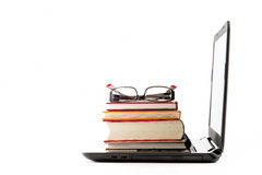Stack of books on laptop. Computer with eyeglasses Stock Photo