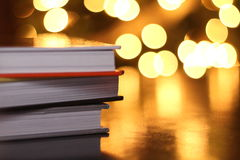 Stack of Books with Lights. A stack of different colored books on a dark table reflect background lights Royalty Free Stock Photo