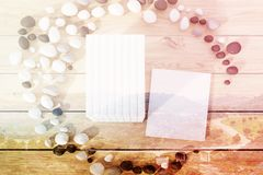 Stack of books lying on a wooden table toned. Top view of a stack of books with blank covers lying on a wooden table inside a crescent made of pebbles. One book Royalty Free Stock Photo