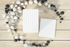 Stack of books lying on a wooden table. Top view of a stack of books with blank covers lying on a wooden table inside a crescent made of pebbles. One book is Royalty Free Stock Photo