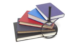Stack of books and magnifying Royalty Free Stock Photos