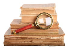 Stack of books, magnifying glass. Stack of books and magnifying glass isolated on white background royalty free stock photo