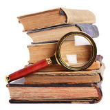 Stack of books, magnifying glass. Stack of books and magnifying glass isolated on white background stock image