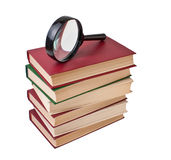 Stack of books and magnifying glass Stock Images